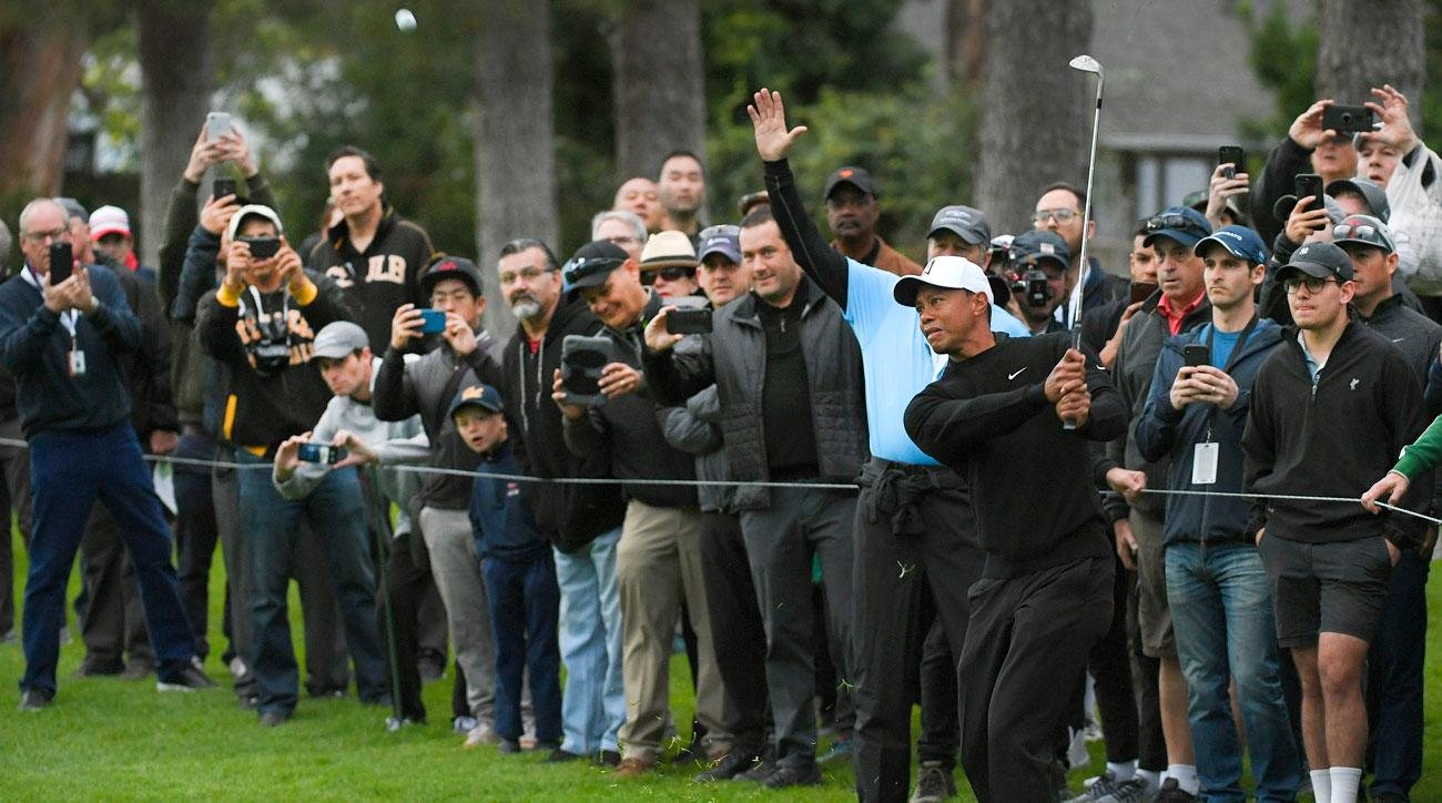 Fans photograph Tiger Woods playing his third shot on the first hole during practice for the Genesis Open.