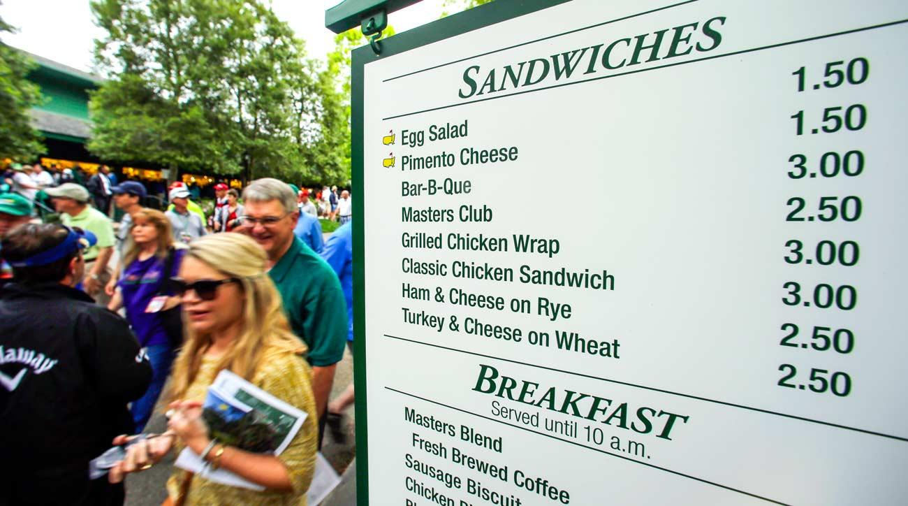 People walk past a vendor sign during a practice round for the 2015 Masters in Augusta, Ga.