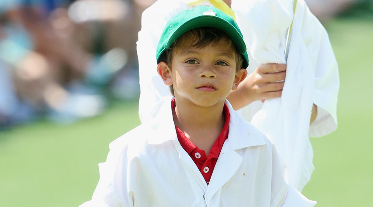 Charlie and Sam Woods works as a caddies for their father Tiger during the Par 3 Contest prior to the start of the 2015 Masters.