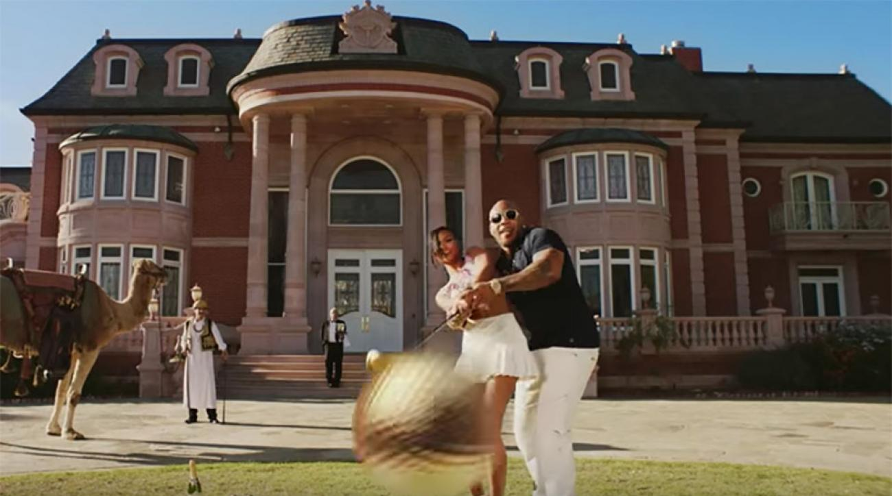 "Flo Rida hits his private tee box complete with gold golf balls and gold-plated clubs in his music video for ""Zillionaire."""