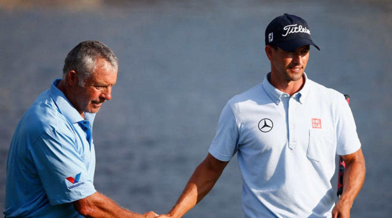 Caddie Steve Williams and Adam Scott shake hands on the 18th green during the second round of the Arnold Palmer Invitational at Bay Hill.