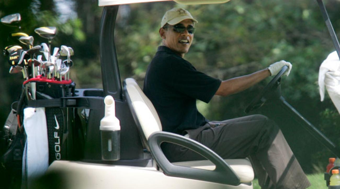 President Obama looks out from his golf cart while playing on the second hole at the Farm Neck Golf Club, in Oak Bluffs, Mass., on the island of Martha's Vineyard in 2009.