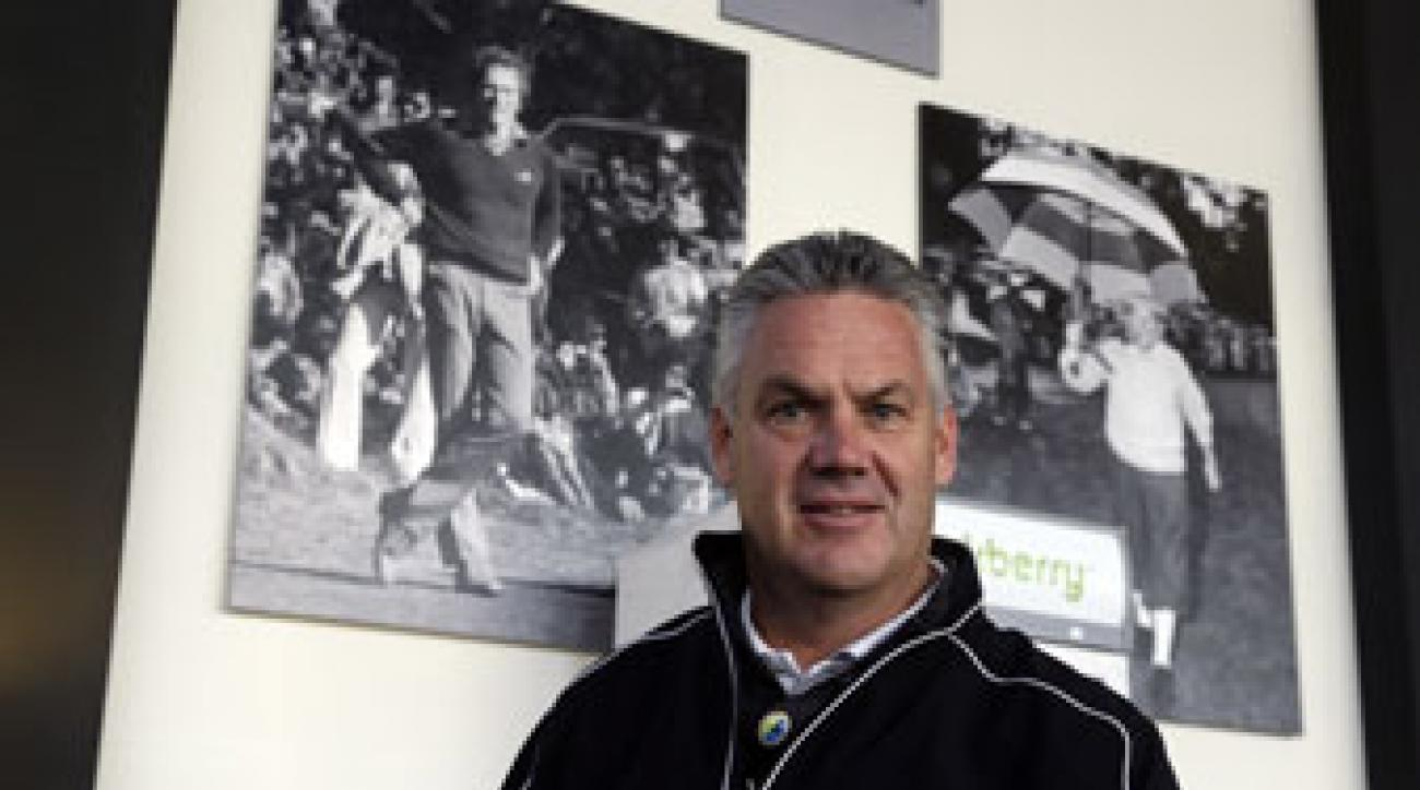 Steve John stands beneath photographs of Clint Eastwood, left, and Bing Crosby, Friday in Pebble Beach.