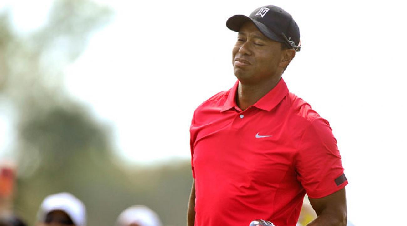 Tiger Woods grabs his back after his drive on the ninth hole in the final round of The Honda Classic. He would later withdraw.