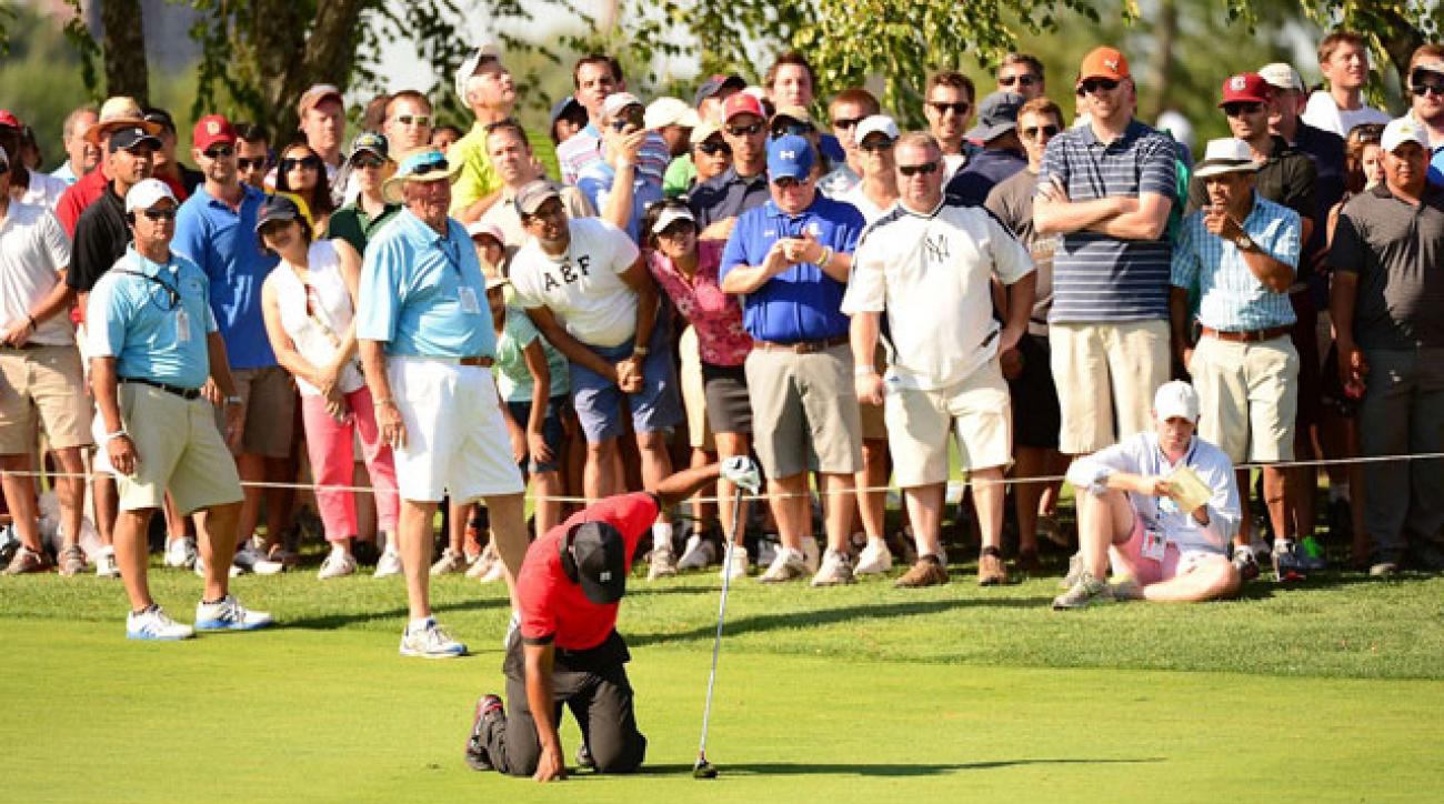 Tiger Woods falls to his knees after suffering back spasms during last August's Barclays at Liberty National Golf Club.