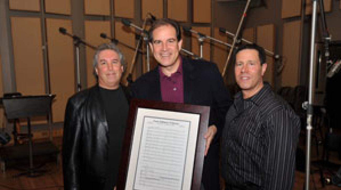 """Rob Aster, left, and David Dachinger, right, collaborate on the music for the Masters. CBS announcer Jim Nantz holds his favorite composition by the duo, """"Fore Fathers."""""""
