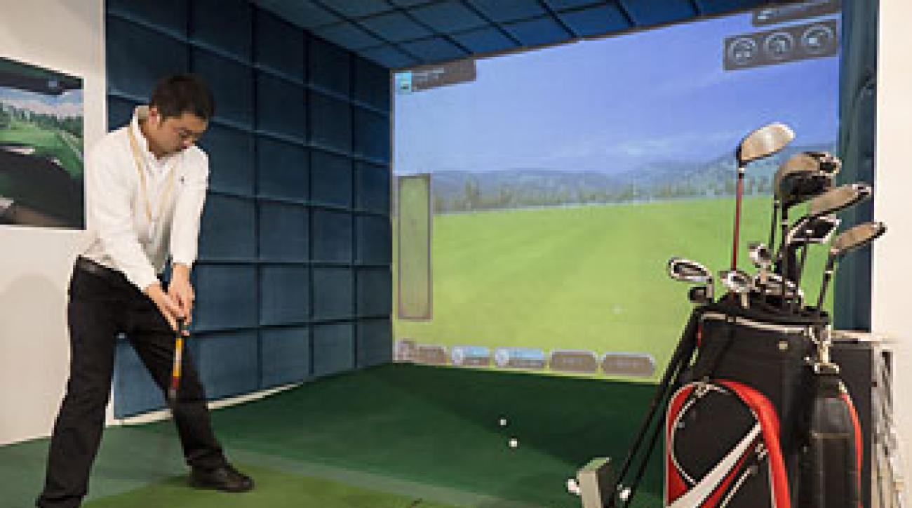 Exhibitors show the latest in golf simulators at the China Golf Show 2013 in Beijing.