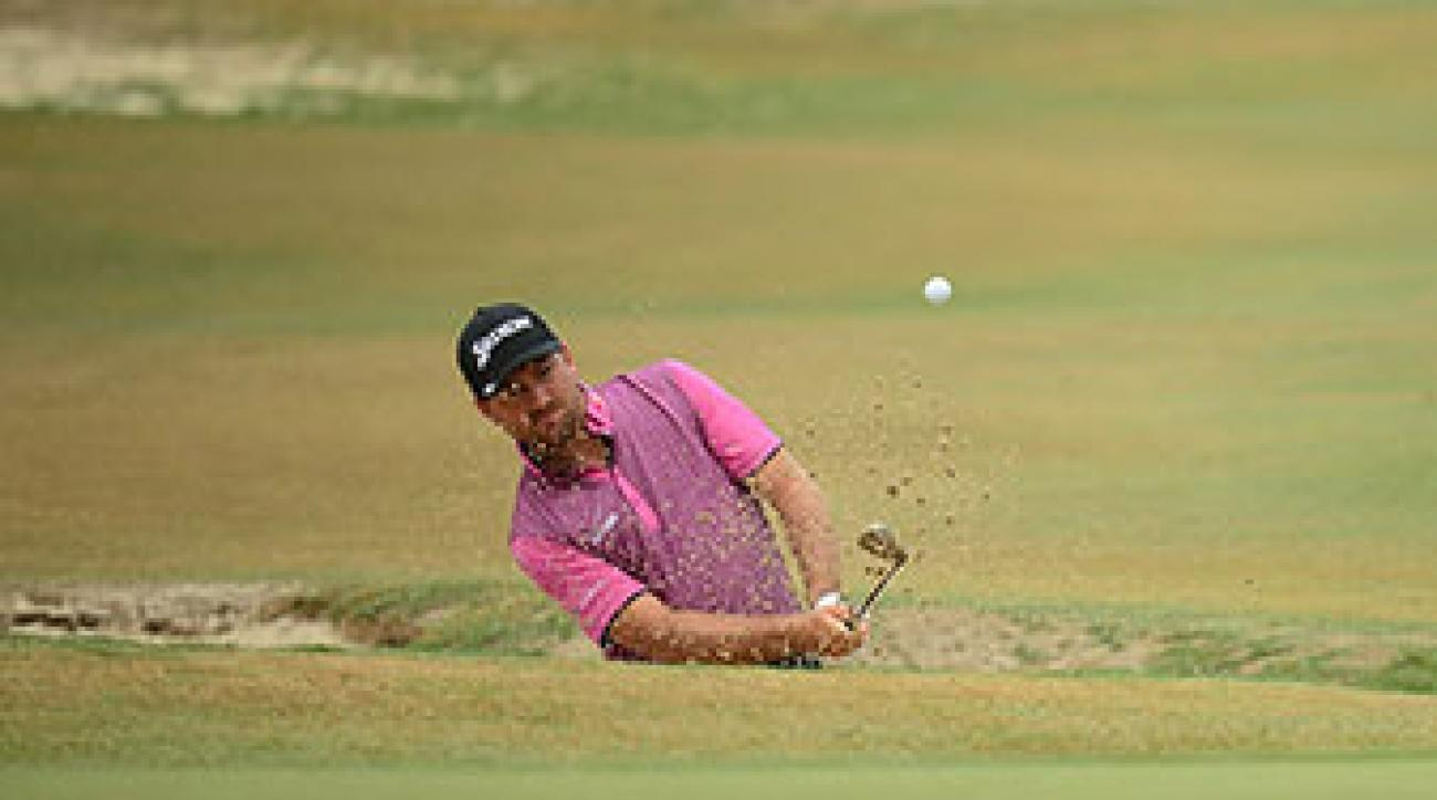 Graeme McDowell chips out of a bunker on the 4th hole at Pinehurst No. 2 on Thursday.