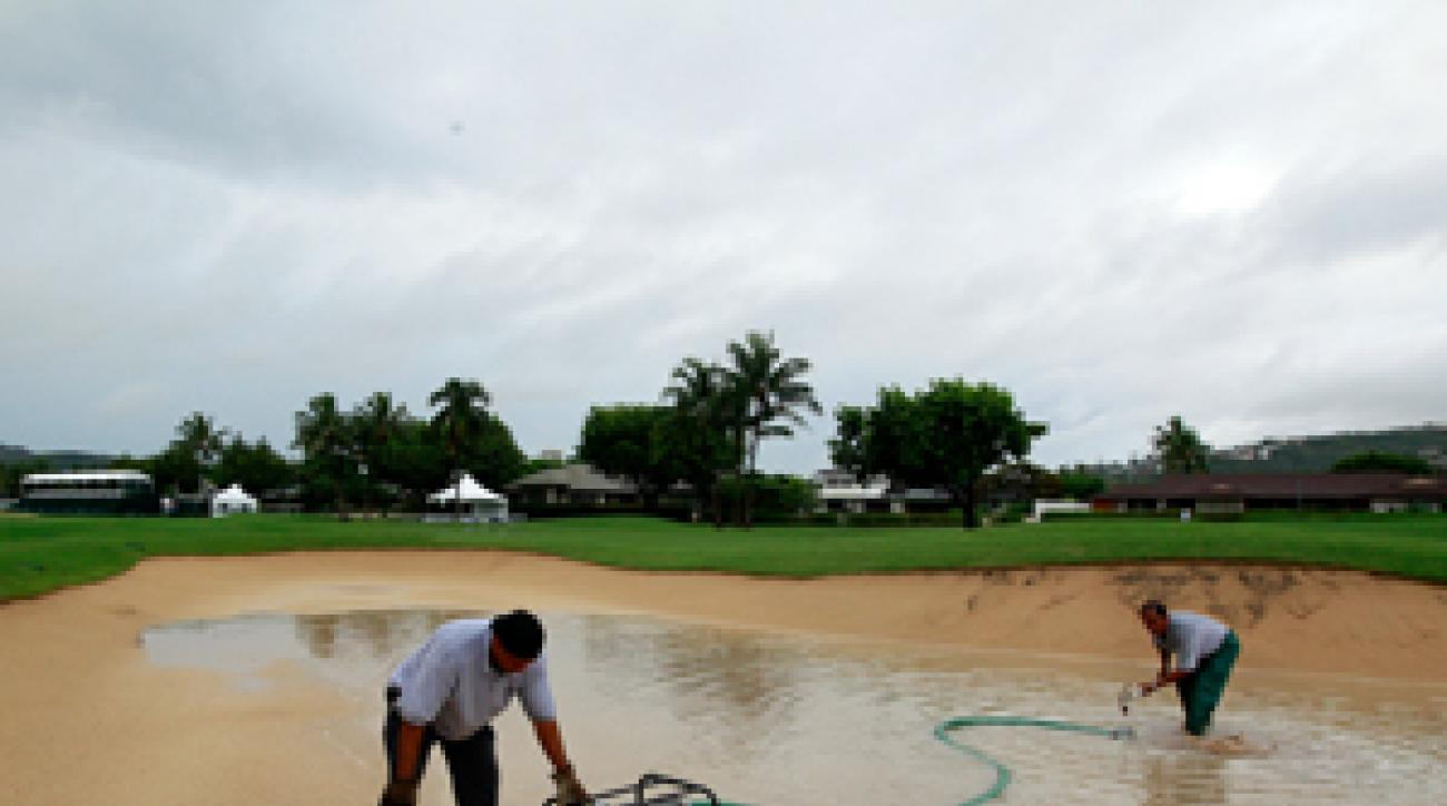 Grounds crews pumped out water from a bunker on the 18th hole Thursday.