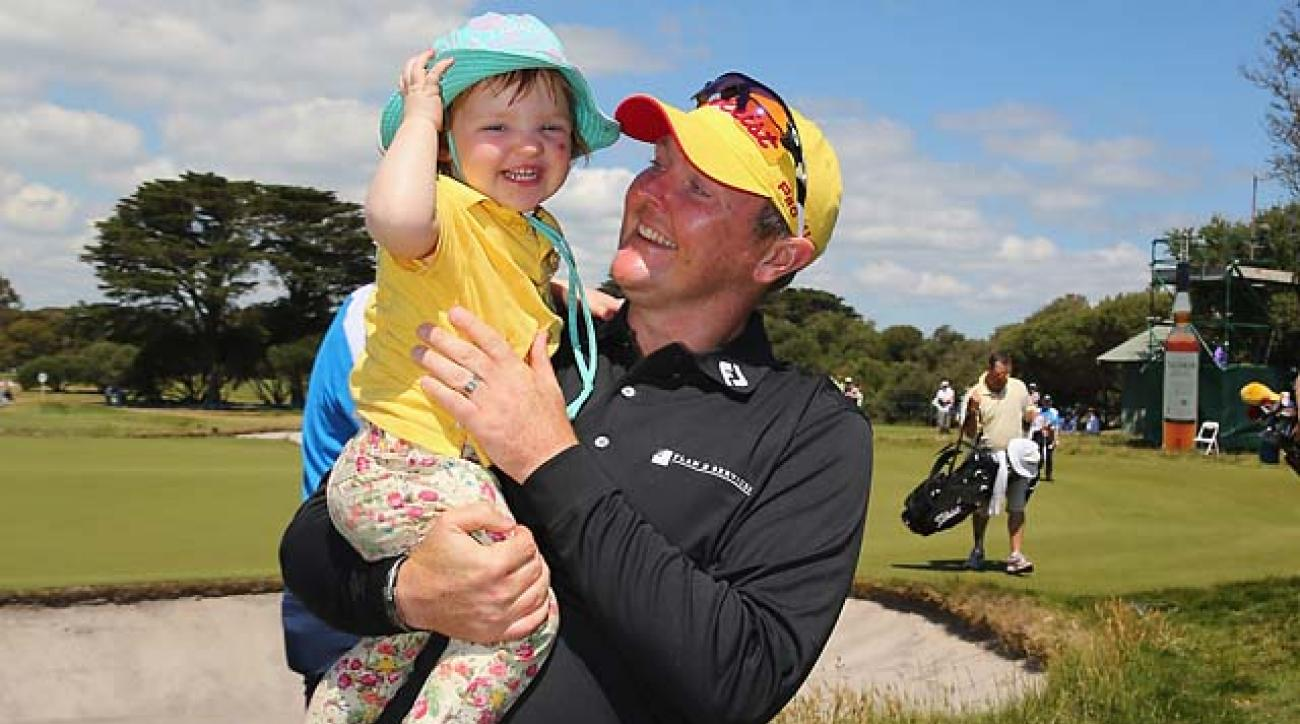 Jarrod Lyle hugs his daughter Lusi on the 18th green after completing the final round of the 2013 Australian Masters.