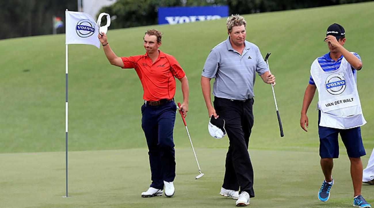 Joost Luiten waves to the crowd on the 18th green following his 5-under 67. Playing partner Dawie Van Der Walt is at right.