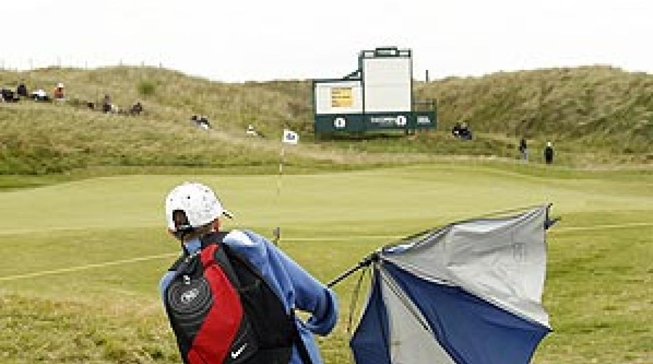 A fan struggled with his umbrella in the wind at Royal Birkdale on Wednesday.