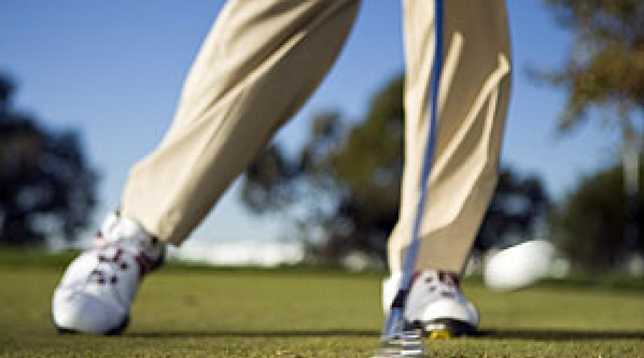 Move your weight left by pressing the spikes on your left shoe into the turf to start your downswing.