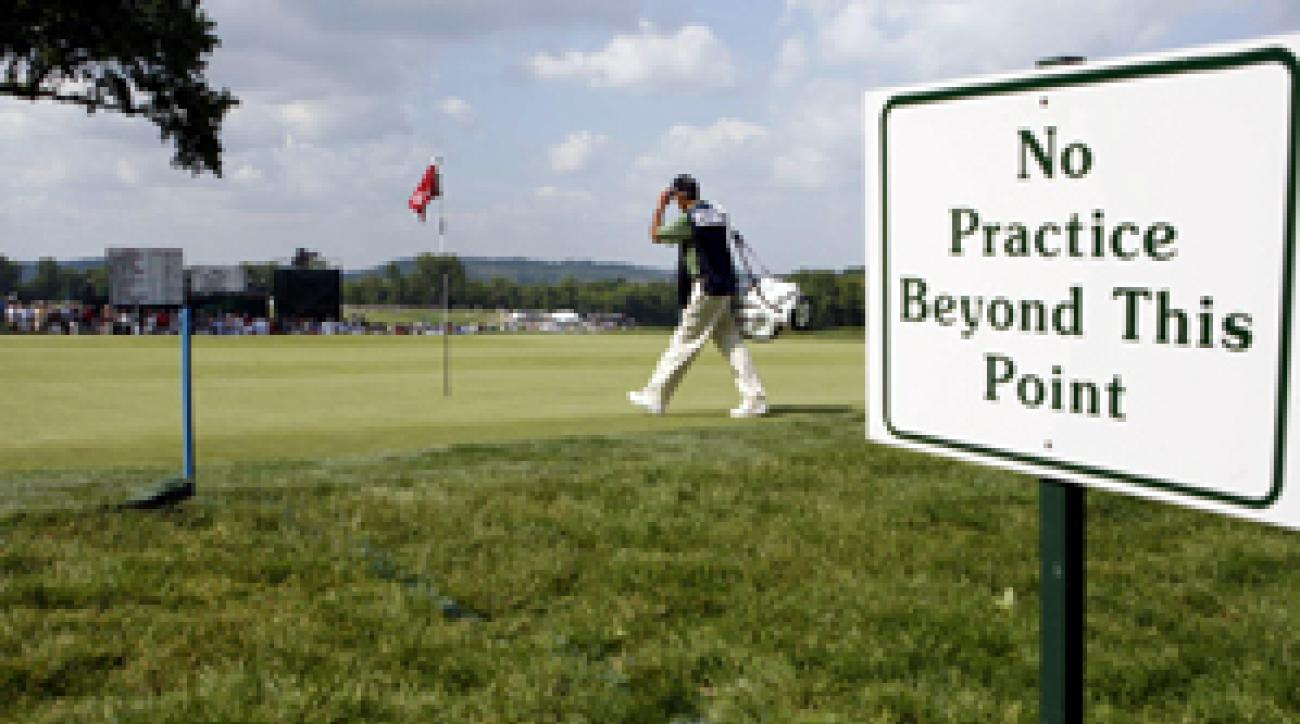 A sign and blue stakes divide the practice green from the real thing on No. 9 at Oakmont.