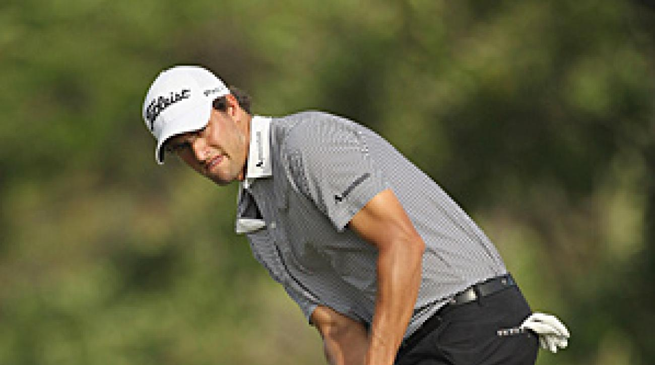 Adam Scott shot his second-straight 65 on Friday at the Singapore Open to take a two-shot lead.