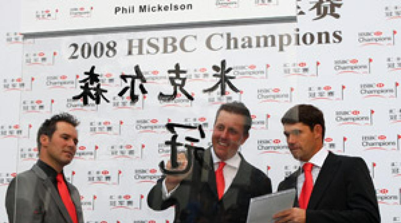 Defending champion Phil Mickelson painted his name in Chinese characters with Trevor Immelman, left, and Padraig Harrington at the Shanghai World Financial Center prior to the start of the HSBC Champions in Shanghai, China.