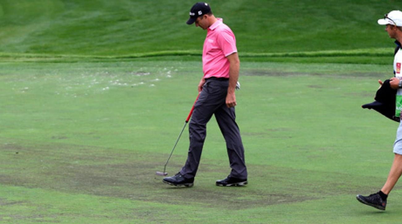 Geoff Ogilvy, left, examined the condition of the ninth green Wednesday during the pro-am at Quail Hollow.