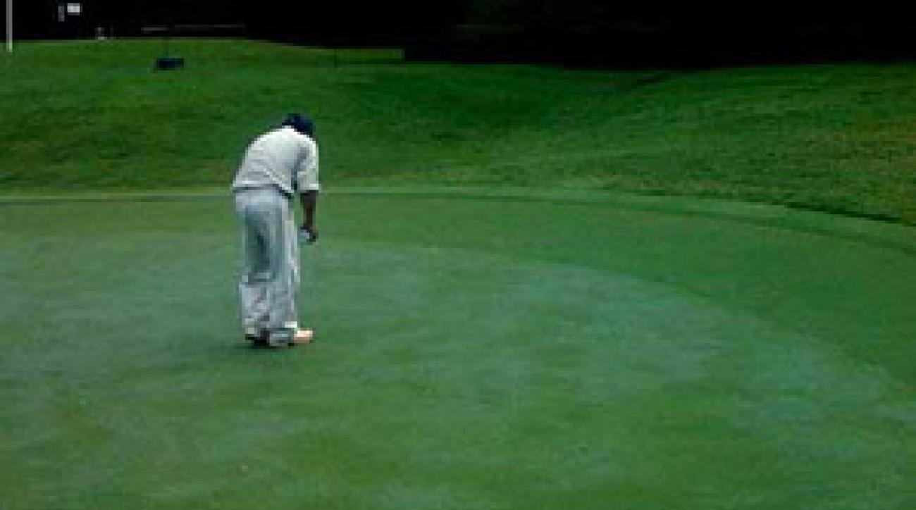 Workers applied a green sandy mix to the putting surfaces where the grass has died.
