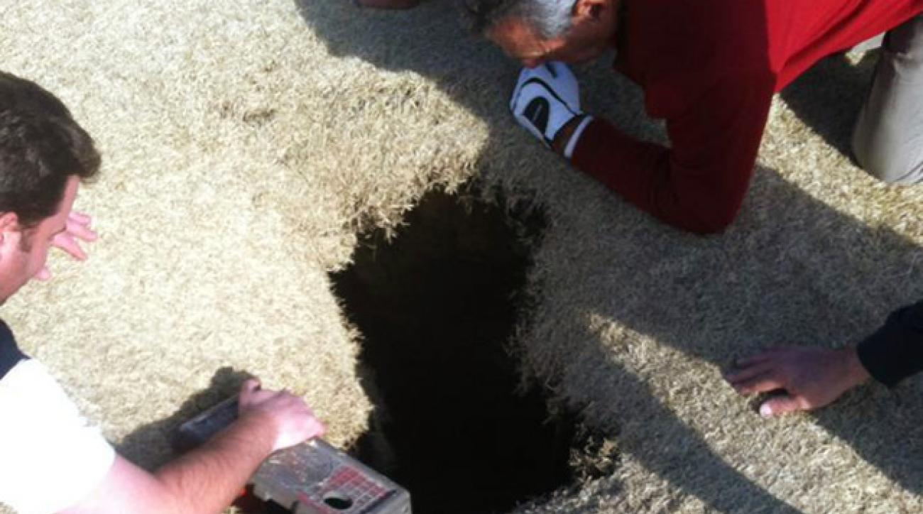 This March 8, 2013 photo provided by Golfmanna shows golfers looking into a sinkhole that opened up under golfer Mark Mihal on a course in Waterloo, Ill.