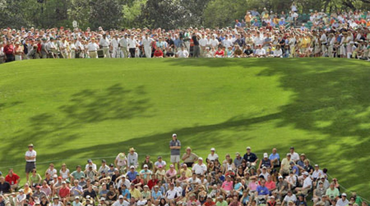 Spectators pack onto the hill below the 6th tee and watch shots soar over their heads, but the author prefers the panorama from behind the tee.