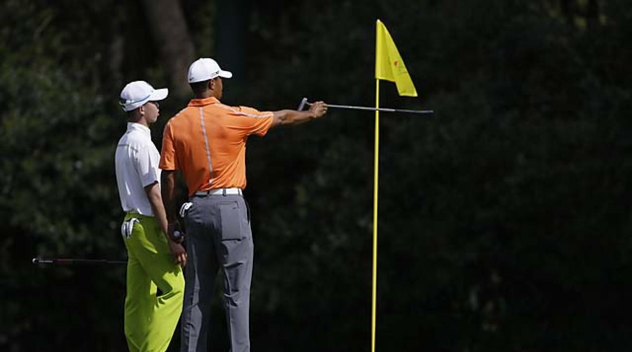 Tiger Woods shares some 'straj' with Tianlang Guan on the 11th green of Augusta National during a practice round Monday. The 14-year-old Guan is the youngest competitor in Masters history.