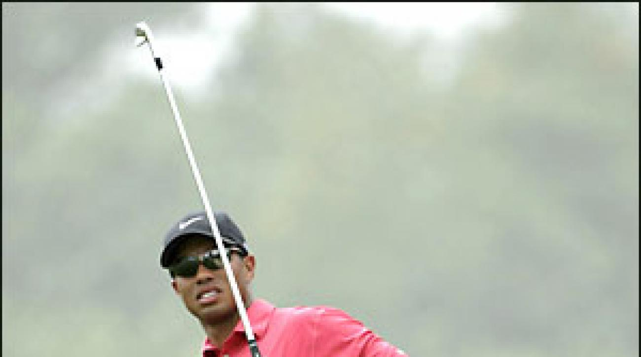 Tiger checks his iron shot during the fourth round of the Dubai Desert Classic.