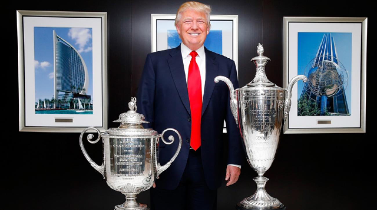 Donald Trump poses with the Wanamaker Trophy and the Alfred S. Bourne Trophy.