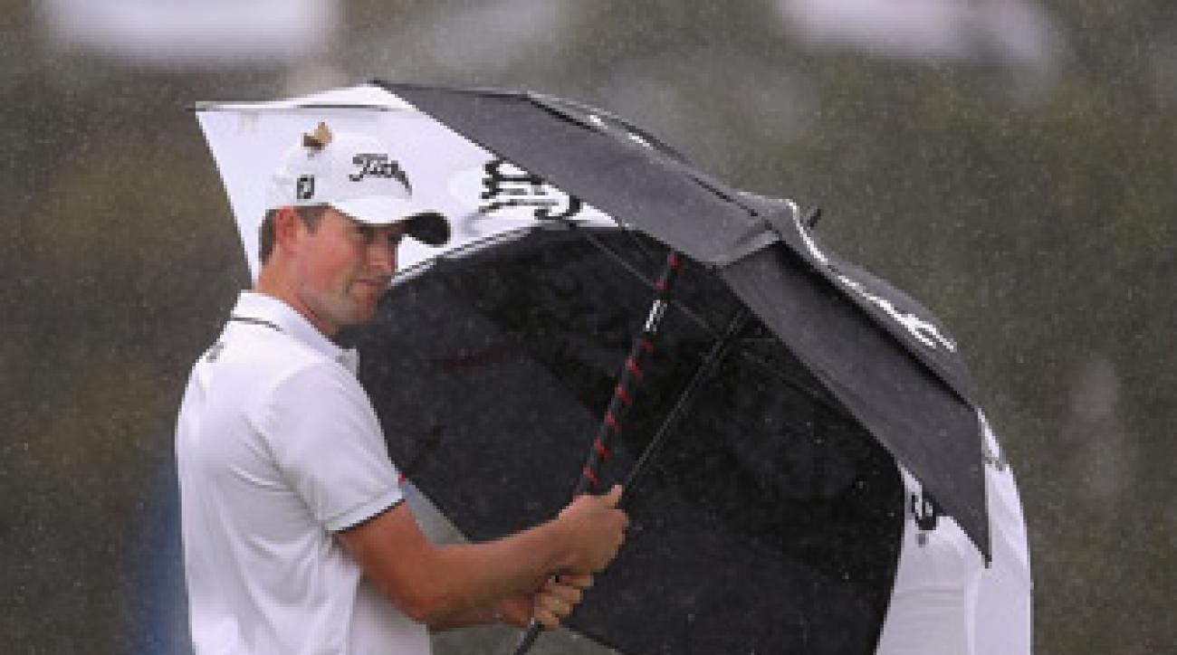 Webb Simpson tried to shield himself from the rain on Friday.
