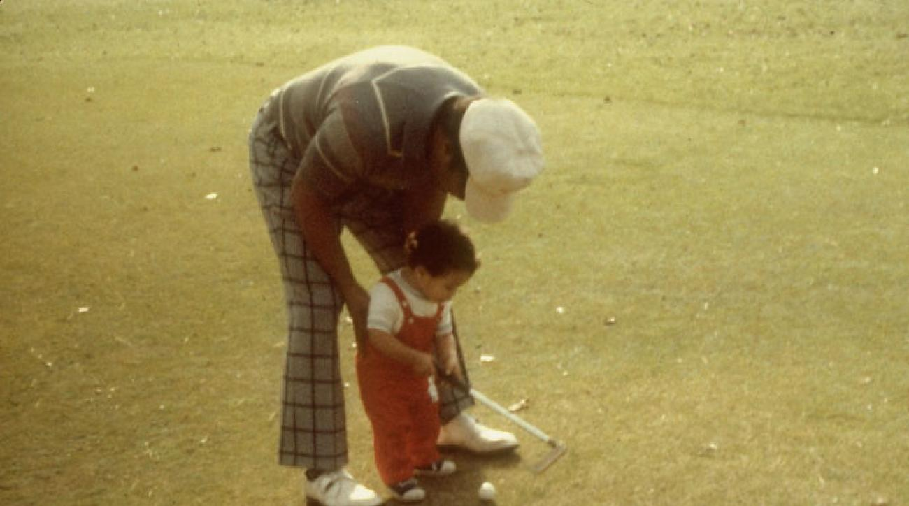A 1-year-old Tiger Woods gets some help from father Earl in an early golf outing.