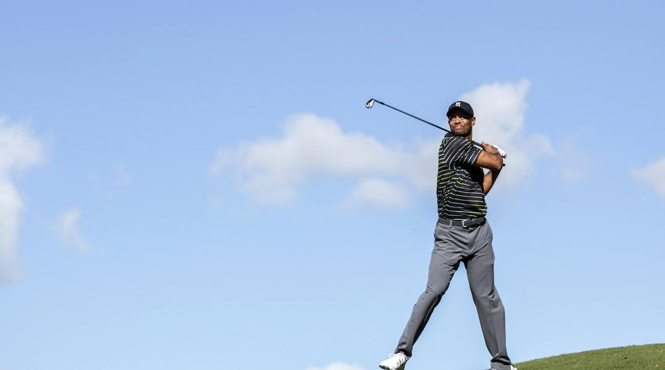 Tiger Woods chips the ball with an awkward follow through on the seventh hole during the first round of the Hero World Challenge golf tournament on Thursday, Dec. 4, 2014, in Windermere, Fla. (AP Photo/Willie J. Allen