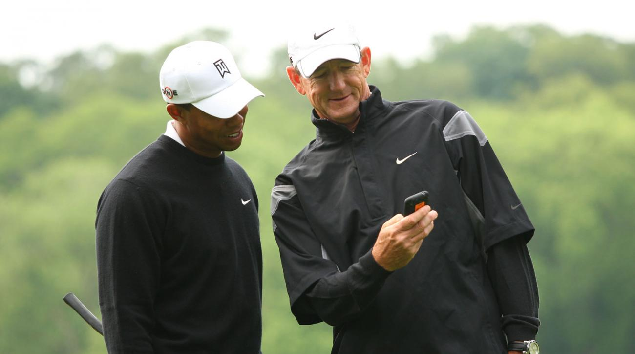 Tiger Woods and his swing coach Hank Haney look at Hank's cell phone during the second day of practice rounds at the 2009 U.S. Open.