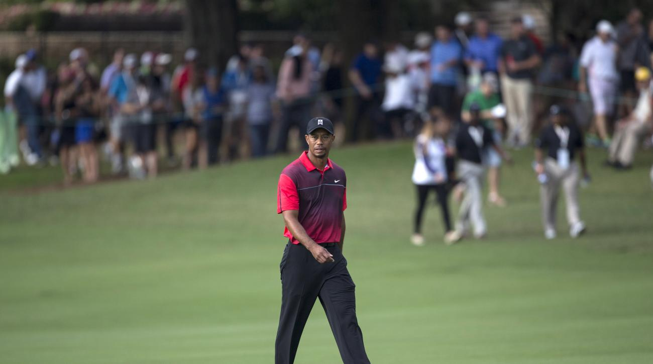 Tiger Woods walks up the 18th fairway to the green during the final round of the Hero World Challenge golf tournament on Sunday, Dec. 7, 2014, in Windermere, Fla. (AP Photo/Willie J. Allen