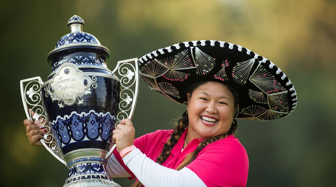 Christina Kim hoists the trophy after her playoff victory at the 2014 Lorena Ochoa Invitational.