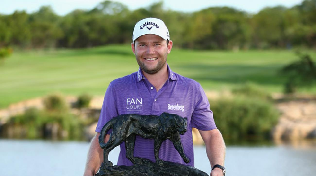 Branden Grace of South Africa hoists the trophy after securing victory in the final round of the Alfred Dunhill Championship at Leopard Creek Country Golf Club in Malelane, South Africa.