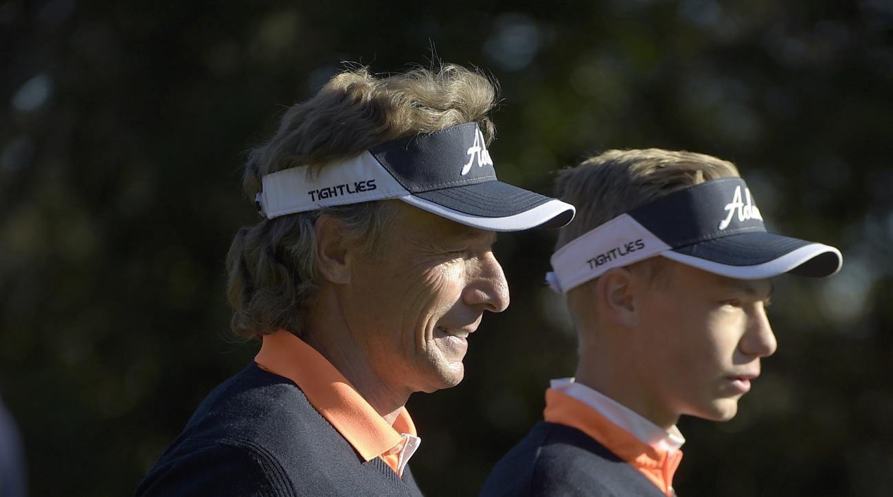 Bernhard Langer, left, of Germany, and his son Jason walk down the first fairway after teeing off during the first round of the Father/Son Challenge golf tournament in Orlando, Fla.