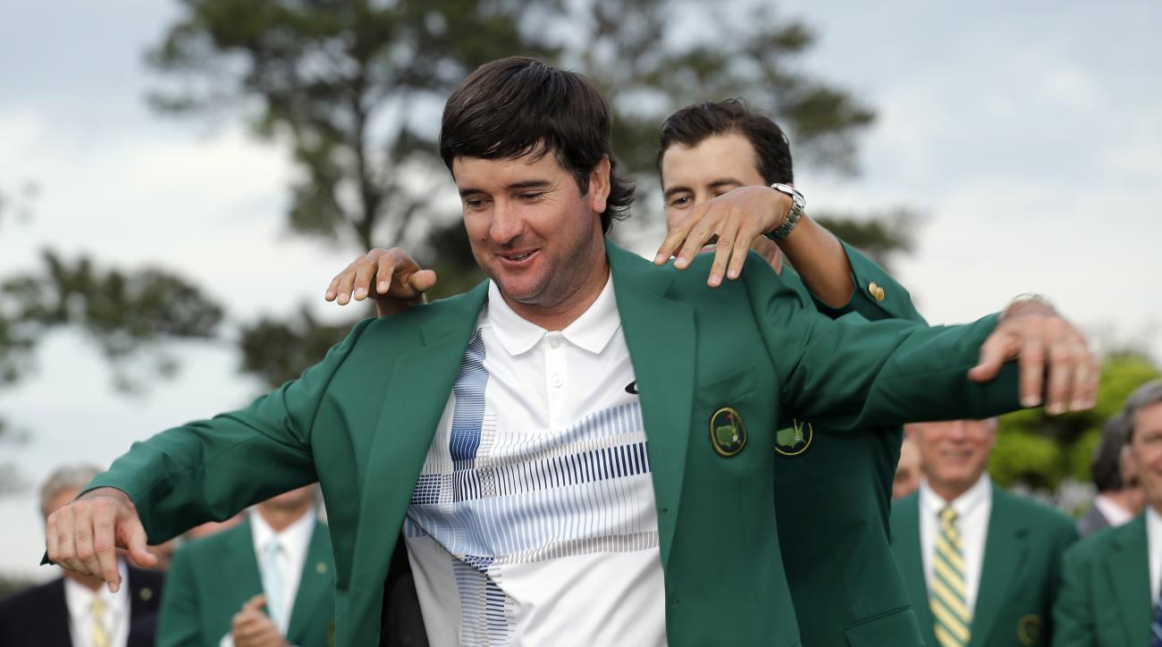 Defending Masters' champion Adam Scott helps Bubba Watson, left, with his green jacket after winning the 2014 Masters.