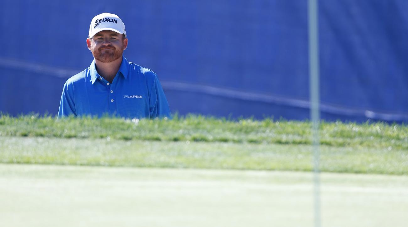 J.B. Holmes plays a shot out of a bunker on the 17th hole during the third round of the Farmers Insurance Open on Saturday.