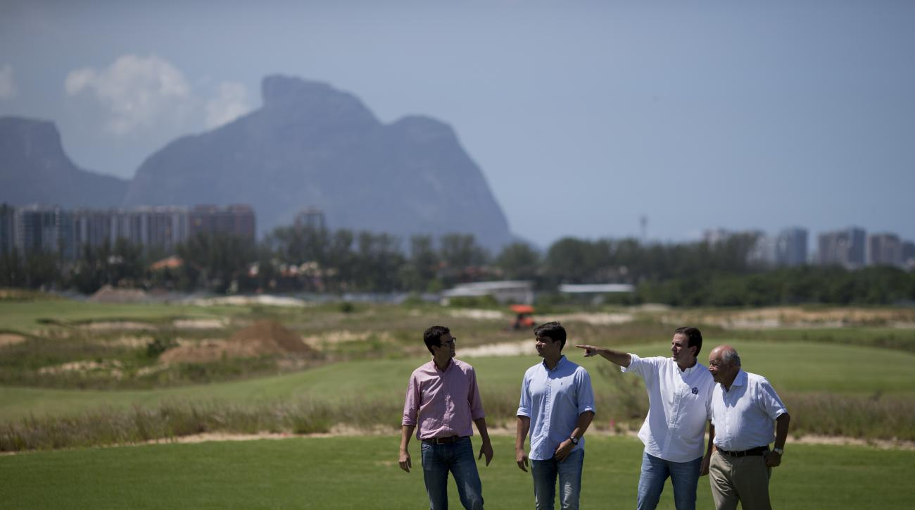 Rio mayor Eduardo Paes, second right, gestures during a visit to the Olympic golf course on Wednesday.
