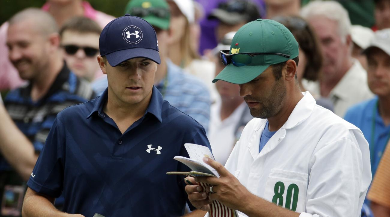 Jordan Spieth checks his course notes with his caddie Michael Greller before teeing off on the sixth hole during the fourth round of the Masters Sunday in Augusta, Georgia.