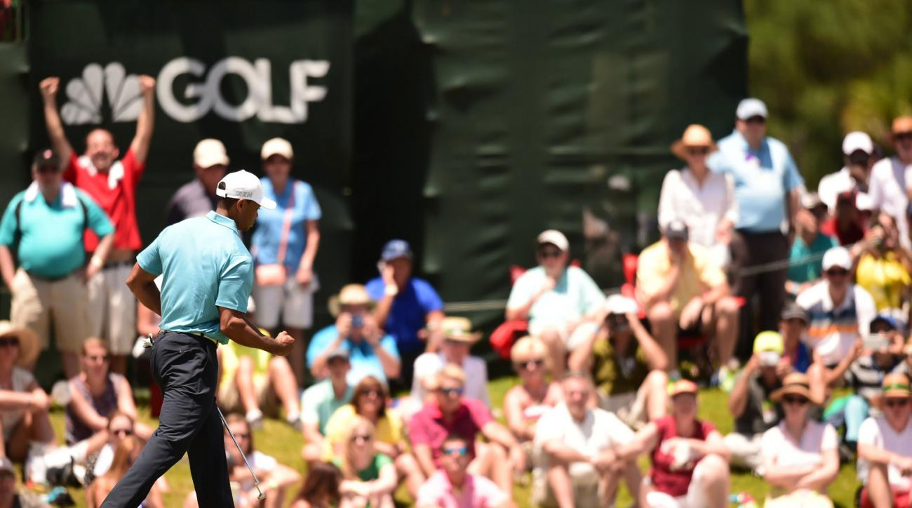 Tiger Woods pumps his fist after sinking a birdie on the 9th hole, his final hole of the day, to make the cut at the Players Championship.