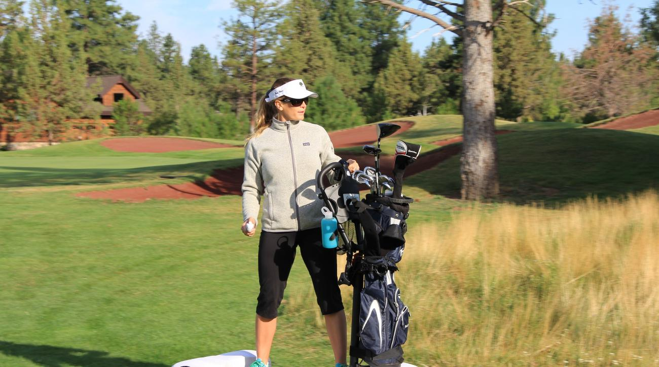 A golfer rides a GolfBoard down the fairway to her next shot.