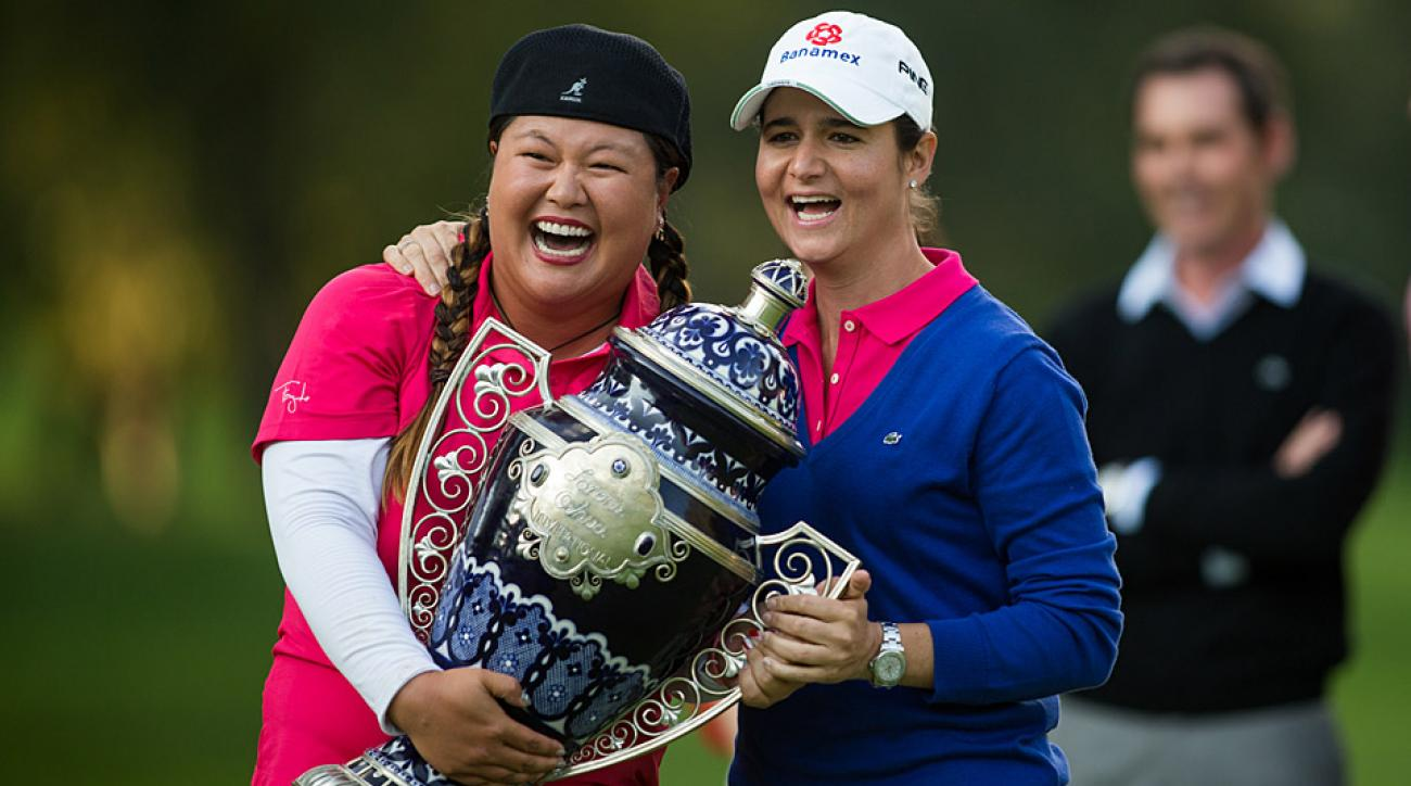 Lorena Ochoa (right) presents Christina Kim with the champions trophy at the 2014 Lorena Ochoa Invitational.