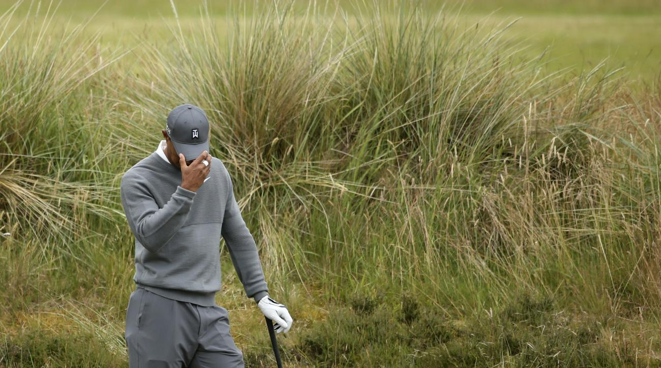 United States' Tiger Woods prepares to take a shot from the rough on the fifth hole during the first round of the British Open Golf Championship at the Old Course, St. Andrews, Scotland, Thursday, July 16, 2015. (AP Photo/Peter