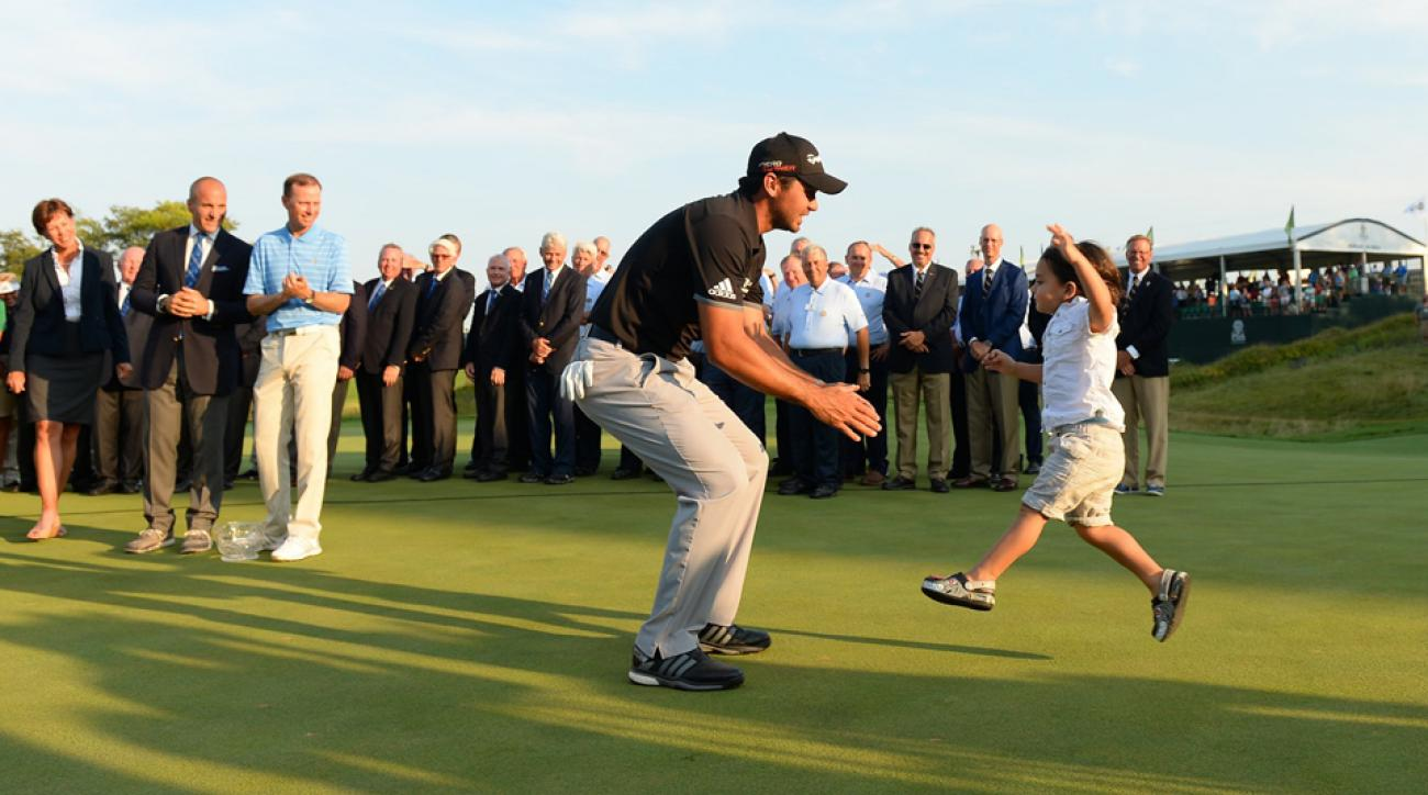 Dash Day jumps into the arms of his father, Jason Day, after Jason won the 2015 PGA Championship at Whistling Straits.