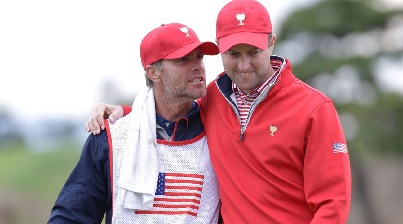 Chris Kirk of the United States celebrates with caddie G.W. Cable after a putt on the 18th hole during the Sunday singles matches at the Presidents Cup.