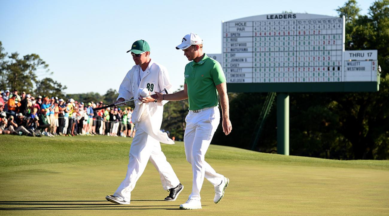 Danny Willett of England and caddie Jonathan Smart walk from the 18th green after finishing during the final round of the 2016 Masters Tournament at Augusta National Golf Club.