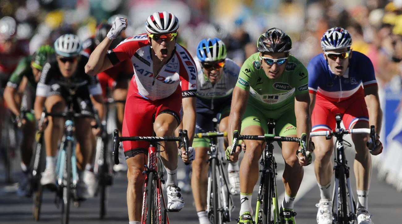 Norway's Alexander Kristoff, center left, crosses the finish line ahead of Peter Sagan of Slovakia, second right, and France's Arnaud Demare, right, to win the twelfth stage of the Tour de France.