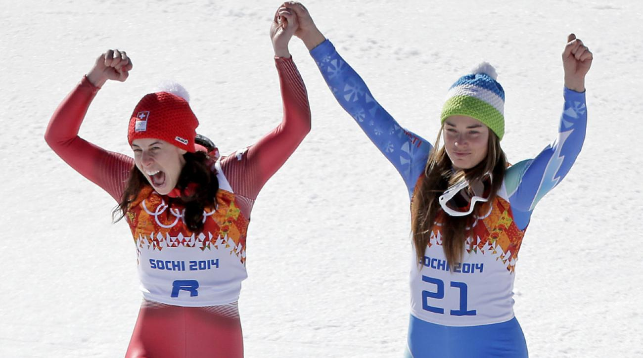 Women's downhill gold medal winners Switzerland's Dominique Gisin, left, and Slovenia's Tina Maze stand together on the podium during a flower ceremony.