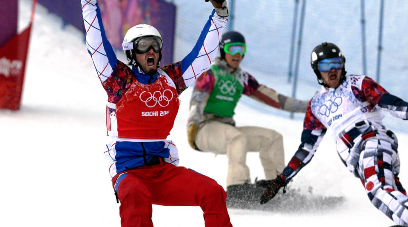 France's Pierre Vaultier, left, celebrates taking the gold medal ahead of silver medalist Nikolai Olyunin of Russia, right, and bronze medalist Alex Deibold of the United States in the men's snowboard cross final at the Rosa Khutor Extreme Park, at the 2014 Winter Olympics, Tuesday, Feb. 18, 2014, in Krasnaya Polyana, Russia.