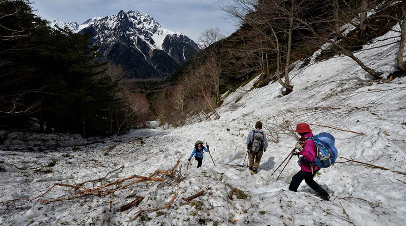 Hikers climbing past avalanche debris near Mount Okuhotaka-dake in the Japanese Alps near Kamikochi, Japan.